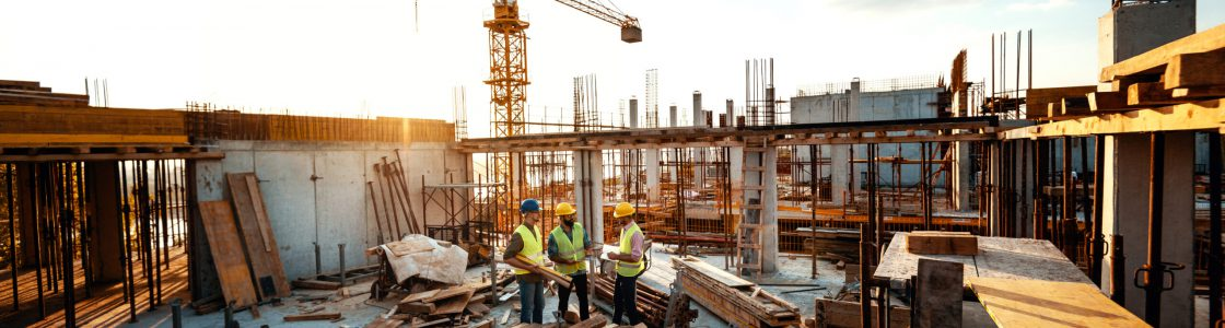 Construction industry concept - architects and engineers discussing work progress between concrete walls, scaffolds and cranes.